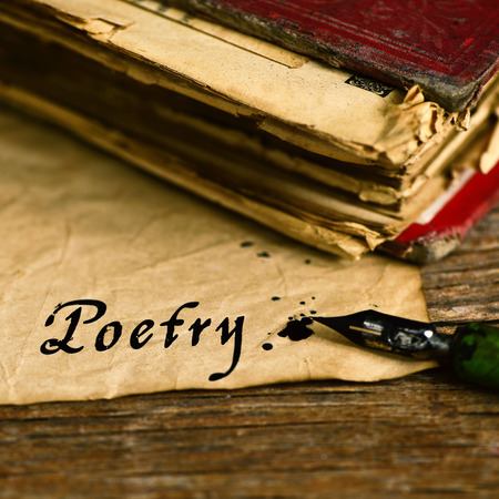 poems: closeup of an old book, an old dip pen and a yellowish paper with the word poetry day written with black ink in it, on a rustic wooden table