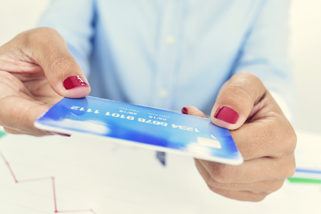 outgoings: closeup of a young caucasian woman, wearing red polished fingernails, with a simulated credit card in her hands, sitting at an office desk