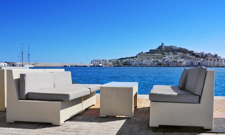 couches: empty couches at the Mediterranean Sea, with Sa Penya and Dalt Vila districts, the old town of Ibiza Town in the background, in the Balearic Islands, Spain Stock Photo