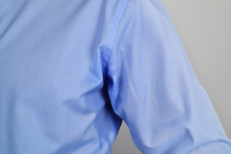 closeup of a man wearing a blue shirt with a sweat stain in his underarm