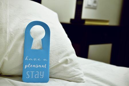 close-up van een blauwe deur hanger met de tekst hebben een aangenaam verblijf geschreven in het, geplaatst op een comfortabel bed