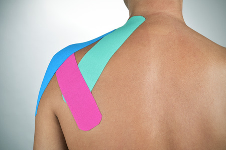 closeup of a young caucasian man with some strips of elastic therapeutic tape of different colors in his back