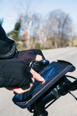 ciclismo: primer plano de un hombre joven que usa un teléfono inteligente montado en el manillar de una bicicleta