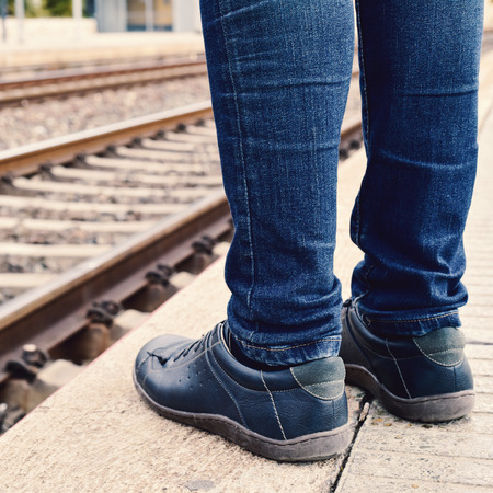 attempting: closeup of the feet of a young man wearing jeans who is waiting for the train at the platform of the train station Stock Photo