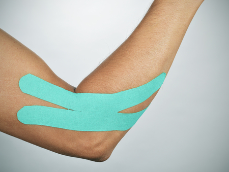 elbow band: closeup of a young man with a blue elastic therapeutic tape in his arm