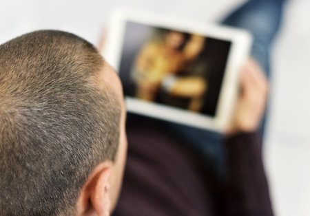 a young caucasian man lying on the couch watches porn in his tablet computer