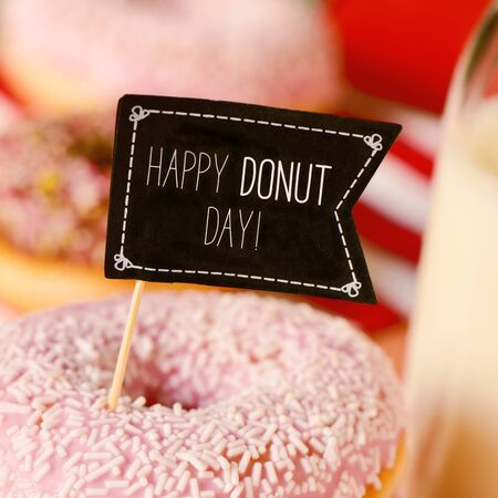 hundreds and thousands: closeup of a black flag-shaped signboard with the text happy donut day in an appetizing donut coated with a pink frosting and white sprinkles Stock Photo