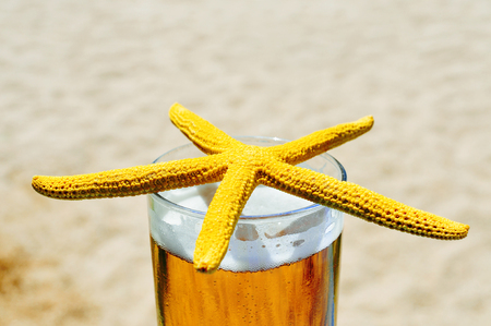thirstiness: closeup of a yellow starfish on a glass with refreshing beer, on the beach