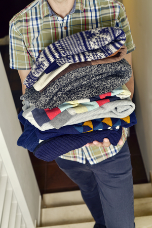 short sleeved: closeup of a young man wearing a short sleeved shirt carrying a pile of different folded sweaters