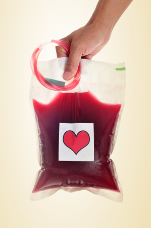 blood plasma: closeup of a young man holding a blood bag with a sticker of a red heart in his hand, against a beige background