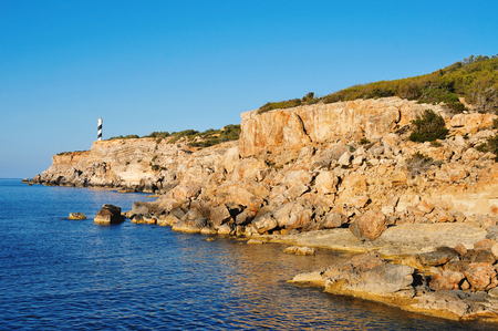northeastern: a view of the Mediterranean Sea, the Far des Moscarter lighthouse and a cliffy landscape of the northeastern coast of Ibiza Island, in the Balearic Islands, Spain