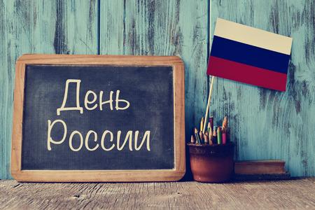 La Journée Russie écrit en russe dans un tableau, et un drapeau de la Russie, sur une table en bois rustique Banque d'images - 59452047