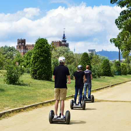 a two wheeled vehicle: Barcelona, Spain - May 30, 2016: Tourists taking a segway tour at the Parc de la Ciutadella in Barcelona, Spain, with the Castell dels Tres Dragons in the background Editorial