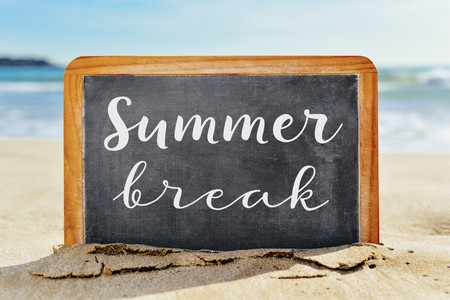 Close-up van een krijtbord met een houten frame en de tekst zomerpauze geschreven daarin, geplaatst op het zand van een strand