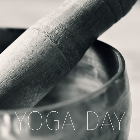 rin gong: closeup of a tibetan singing bowl with its wooden mallet, in duotone, and the text yoga day