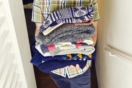 homemaking: closeup of a young man wearing a short sleeved shirt carrying a pile of different folded sweaters