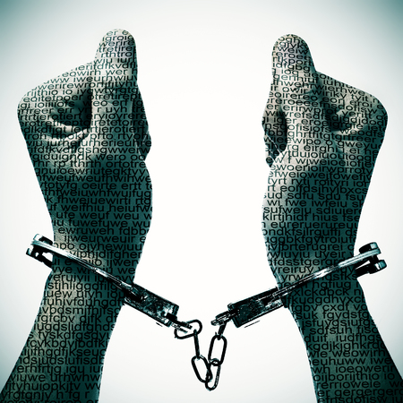 rights: closeup of a handcuffed man with his hands and wrists patterned with no-sense words Stock Photo