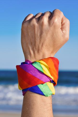 lesbienne: gros plan d'un jeune homme caucasien avec son poing levé vers le ciel et un foulard à motif que le drapeau arc-lié en elle, avec l'océan en arrière-plan Banque d'images