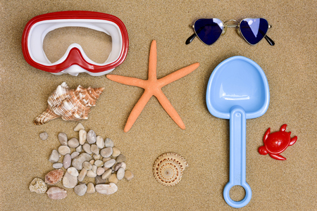 stuff toy: high-angle shot of some summer stuff, such a diving mask, a starfish, a pair of heart-shaped sunglasses, a toy shovel, some conchs and some pebbles, on the sand of a beach