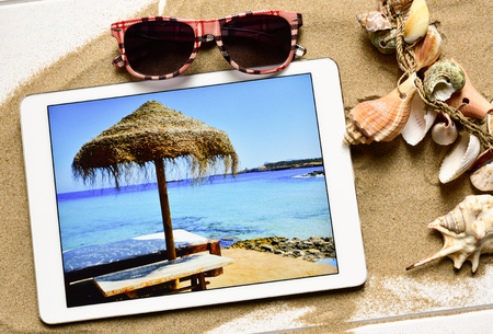 high-angle shot of a white wooden surface full of sand and an ornament made with different conchs and seashells, a pair of sunglasses and a tablet computer with the picture of a beach taken by myself Stock Photo