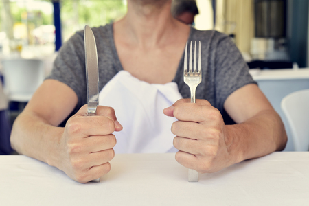 dinnertime: closeup of a young caucasian man sitting at a table waiting for the food, with a knife in one hand and a fork in the other hand