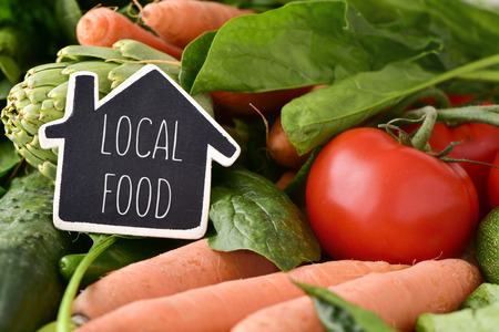 close-up van een huis-vormig bord met de tekst lokale gerechten die op een stapel van een aantal verschillende rauwe groenten, zoals komkommers, tomaten, wortelen en artisjokken, op een rustieke houten tafel Stockfoto