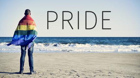 言葉誇りと若い白人男が後ろから見た海を見て虹の旗に包まれて 写真素材