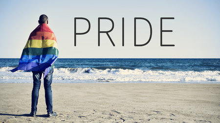 the word pride and a young caucasian man seen from behind wrapped in a rainbow flag looking at the ocean