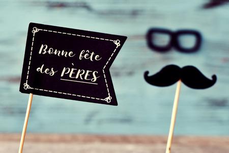 eine schwarze Flagge förmige Schild mit dem Text Text bonne fete des peres, glücklicher Vatertag in französisch, und einen Schnurrbart und eine Brille das Gesicht eines Mannes, vor einem blauen Hintergrund rustikalen bilden Standard-Bild