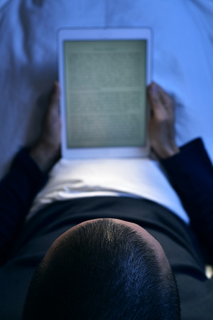 prose: a young caucasian man lying in bed reads an e-book in his tablet computer, at night Stock Photo