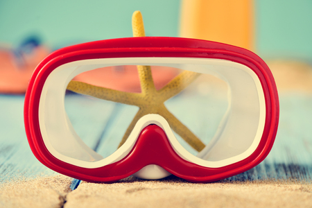 diving mask: closeup of a red and white diving mask on a pile of sand and a yellow starfish, placed on a rustic blue wooden surface