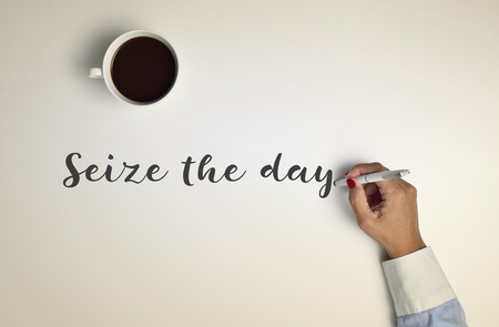 seize: high-angle shot of a cup of coffee on an off-white surface and a young woman writing the text seize the day with a pen