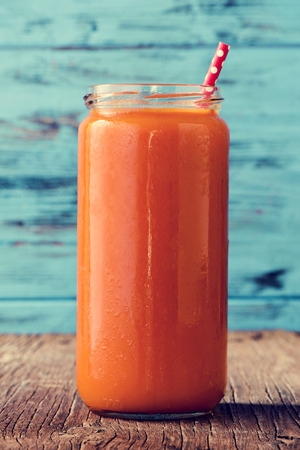 closeup of an orange detox smoothie served in a glass jar with a red drinking straw patterned with white dots, on a rustic wooden surface