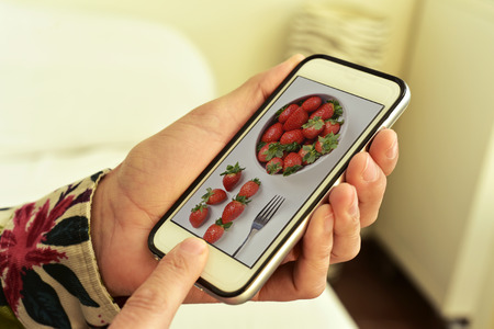 ins: closeup of a young caucasian man with his smartphone ins his hands, with a picture of a bowl with strawberries, taken by myself, in its screen