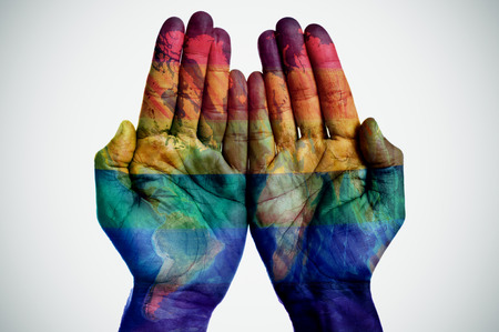 rights: the palms of a young man put together patterned with a world map and a rainbow flag