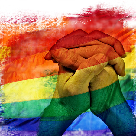 lesbianism: double exposure of a rainbow flag and the hands of a young man put together like praying