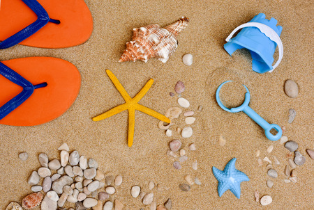 stuff toy: high-angle shot of some summer stuff, such a pair of flip-flops, a conch, a starfish, some pebbles and seashells or a small beach pail and a toy shovel, on the sand of a beach