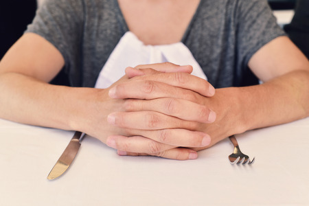 dinnertime: closeup of a young caucasian man sitting at a table waiting for the food, with his hands clasped a and a knife and a fork in front of him