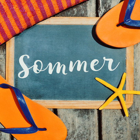 sommer: high-angle shot of a pair of orange flip-flops, a starfish, a beach towel and a chalkboard with the word sommer, summer in German written in it, on a rustic wooden boardwalk
