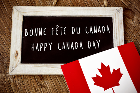 patriot act: the text Happy Canada Day written in French and English in a chalkboard, and a flag of Canada, on a rustic wooden surface