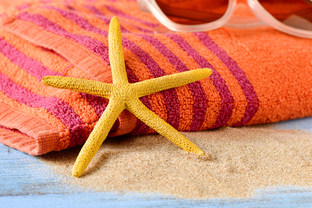 beach towel: closeup of a yellow starfish on a pile of sand, and a pair of sunglasses on an orange beach towel, placed on a rustic blue wooden surface Stock Photo