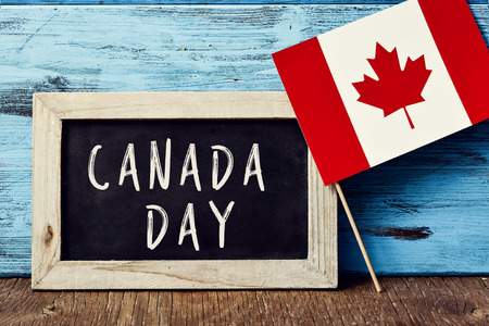 the text Canada Day written in a chalkboard, and a flag of Canada, on a rustic wooden surface