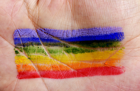 rainbow flag: closeup of the palm of the hand of a young caucasian man with a rainbow flag painted in it Stock Photo
