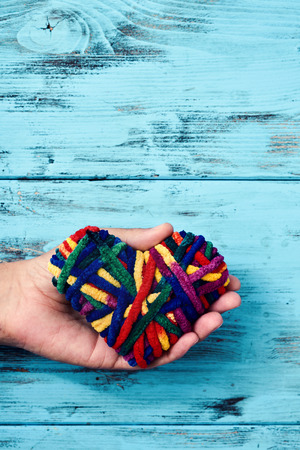 closeup of a young caucasian man holding a heart wrapped with a rainbow-patterned ribbon in his hand, against a blue rustic wooden background