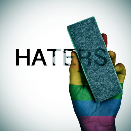 lesbianism: closeup of a man with his hand patterned as the rainbow flag deleting the word haters with an eraser