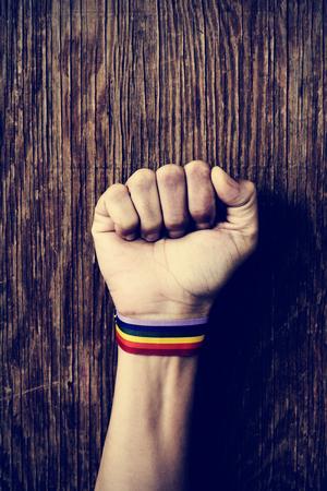 bandera gay: primer plano de un hombre caucásico joven con una banda modelada como la bandera del arco iris atado a su muñeca y el puño levantado contra un fondo de madera rústica