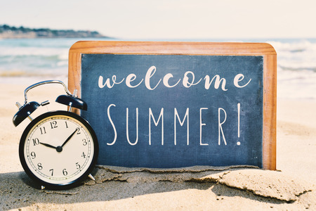 closeup of retro alarm clock and a chalkboard with the text welcome summer written in it, placed on the sand of a beach