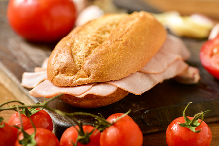 panino: closeup of a braised turkey ham sandwich on a rustic wooden table next to some fresh tomatoes Stock Photo