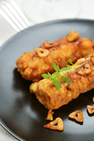 pescado: closeup of some battered and fried cod fillets covered with fried garlic served in a black plate Stock Photo