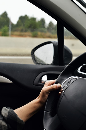 travelling salesman: closeup of a young caucasian man driving a car in a road with several lanes, in a rainy day Stock Photo